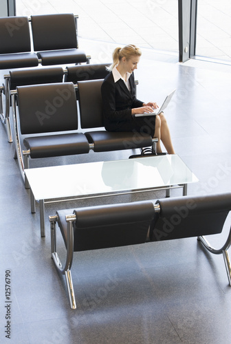 A businesswoman in waiting room, typing on a laptop