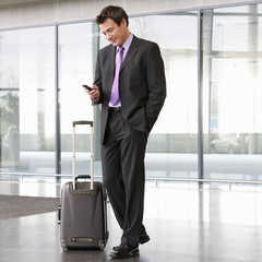 A businessman standing with a suitcase talking on a mobile phone