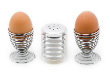 Two eggcups with a salt can in the middle, isolated on white