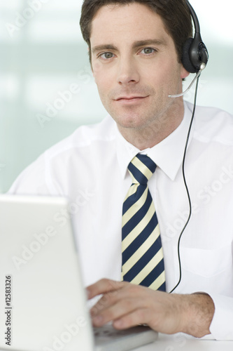A man wearing a headset typing on a laptop