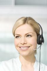 A blonde woman wearing a telesales headset
