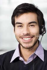 A dark haired male wearing a telesales headset