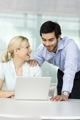 Two business colleagues looking at laptop, smiling