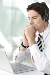 A man wearing a headset looking at a laptop