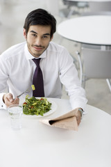 A man reading a newspaper whilst having his lunch