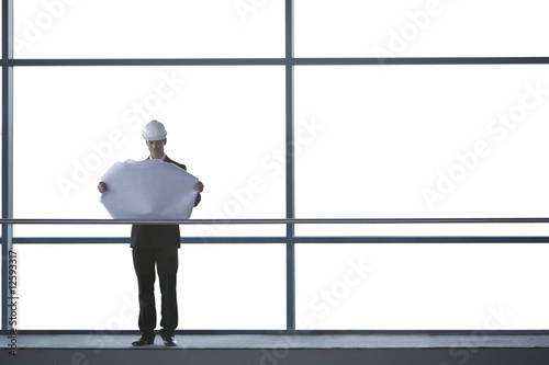 An architect on walkway of office building, looking at plans