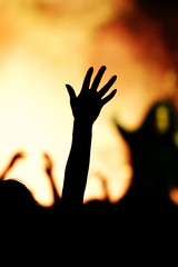 young woman throws hand in the air at a concert