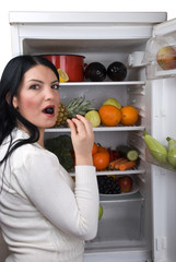 Woman eat a berry grape from fridge