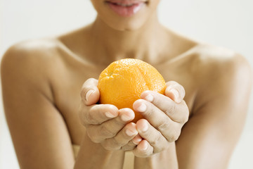A woman holding an orange in both hands