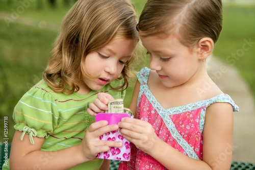 Two little twin girls find a dollar note inside a box
