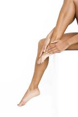 Woman rubbing her feet, applying moisturizer