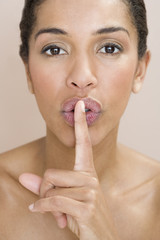 A woman holding finger to her lips, gesturing for silence