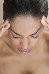 A woman with a migraine, fingers pressed to forehead
