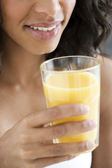 A woman holding a glass of orange juice