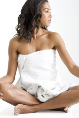 A young woman sitting cross-legged, wrapped in a towel
