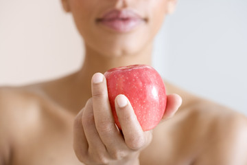 A woman holding a red apple