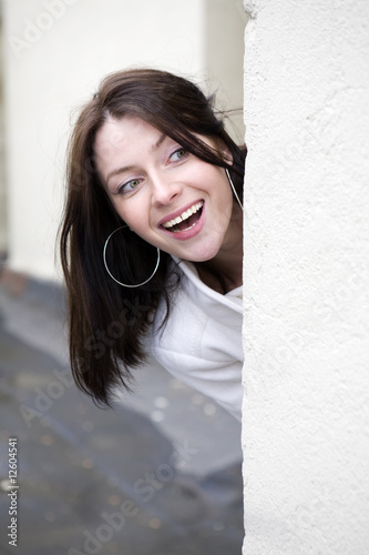 attractive young woman  peeking around the corner at house