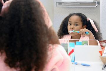 Girl brushing teeth in mirror.