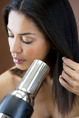 A young woman blow drying her hair