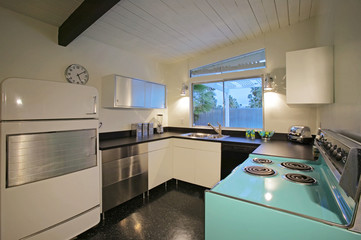 Electric stove placed opposite to the refrigerator in an elegant kitchen
