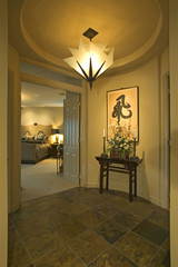 A sumptuous lamp is suspended from the ceiling outside the bedroom