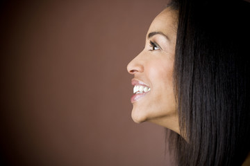 Portrait of a young black woman with long straight hair smiling