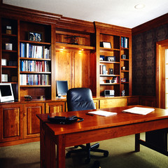 Large bookshelves in an office with a phone and newspaper placed on a desk