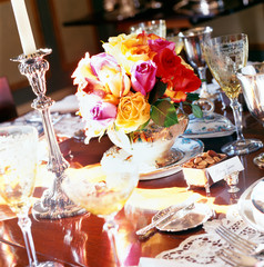 Centerpiece of Roses Surrouned by Wine Glasses and Table Settings
