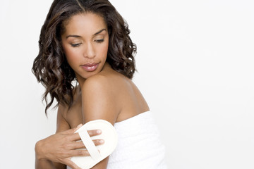 A woman buffing her skin with an exfoliating mitt