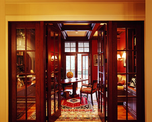 An open door leads to a red colored room with table placed centrally inside