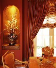 An elegant flower vase is seen near the curtains while candles are put on the dining table