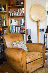 Worn Leather Club Chair by Bookcase