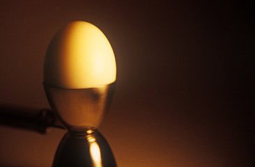 A boiled egg sits in a stainless-steel egg cup