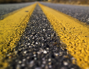 Two yellow lines are seen painted on a tar road