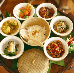 High angle view of various bowls containing delicious foods placed on a wooden table