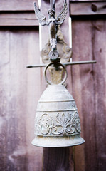 Angel Figure on Top of Decorative Bell Hanging on Fence
