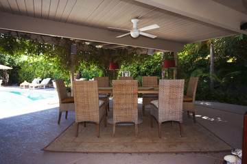 Covered Outdoor Dining Area with Pedestal Table and Wicker Dining Chairs