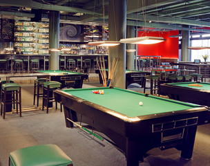 Interior of a club having pool tables illuminated with lights