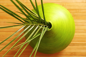 Lime green vase with palm fronds on wooden table