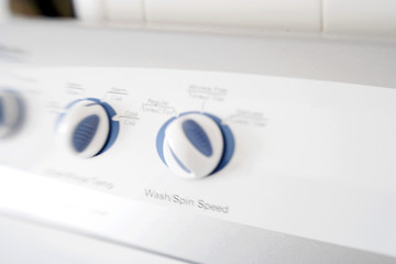 Blurred dials and settings on white washing machine