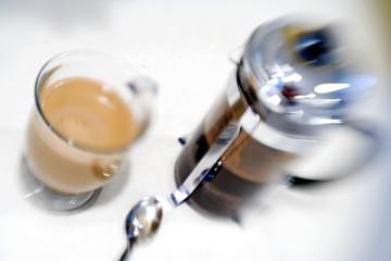 Blurred French press and filled glass mug