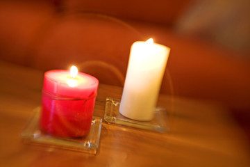 Lit red and white candles on brown wood table