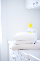 White towels stacked on washer/dryer unit