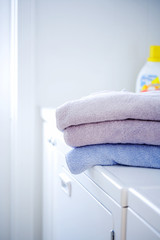 Stack of pastel towels on washer and dryer unit
