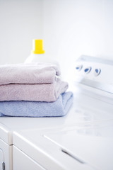 Folded towels and detergent on white washer and dryer