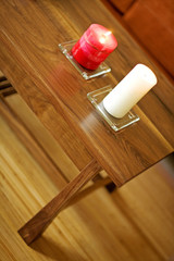 Tilted view of wooden coffee table with lit candles