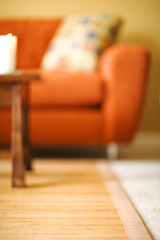 Blurred orange couch in yellow hardwood living room
