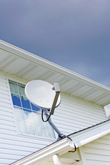 Small satellite dish on roof of white multi-story house
