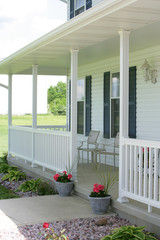 Front porch of multi-story house with white siding