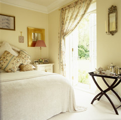 French Doors Lead to A Garden From a Cozy Bedroom